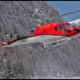 Red Helicopter Landing in the Snow at the Base of a Mountain